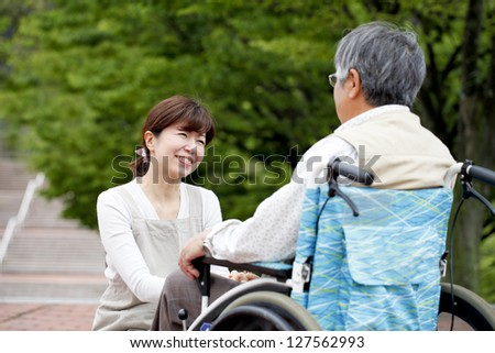 Women assisted wheelchair - stock photo