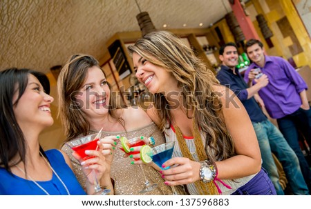 Women at the bar having drinks and men looking at them - stock photo
