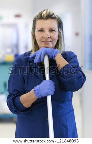 Women at work, portrait of happy professional female cleaner smiling and looking at camera in office. Three quarter length - stock photo