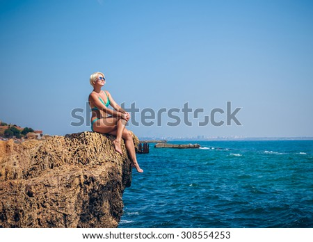 Women Athlete on a rock by the sea against the sky - stock photo