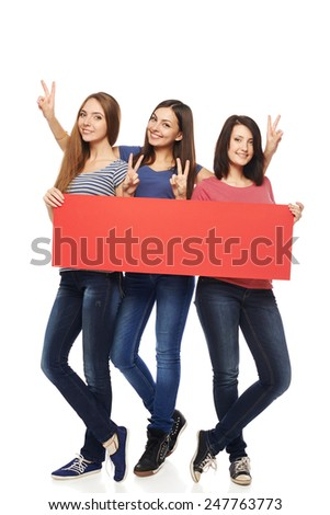 Women billboard sign. Fill length of three excited women showing blank red placard and gesturing V sign, over white background - stock photo