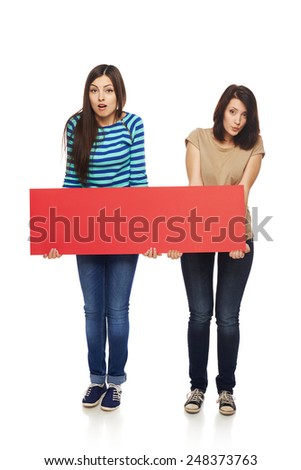 Women billboard sign. Fill length of two surprised women holding blank red banner, over white background - stock photo