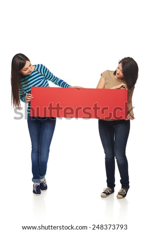 Women billboard sign. Fill length of two young casual women holding blank red placard and looking at it, over white background - stock photo