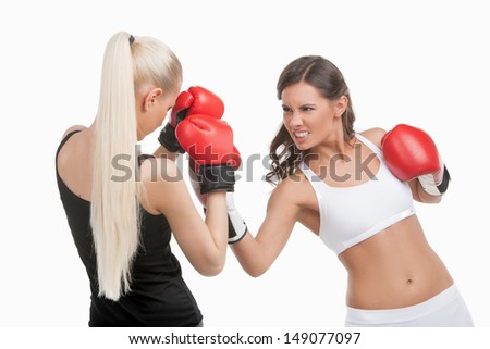 Women boxing. Two young confident women boxing while isolated on white - stock photo