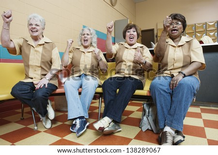 Women cheering at bowling alley - stock photo