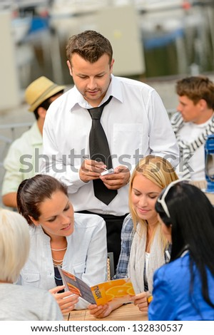 Women customers ordering from waiter at sidewalk restaurant - stock photo