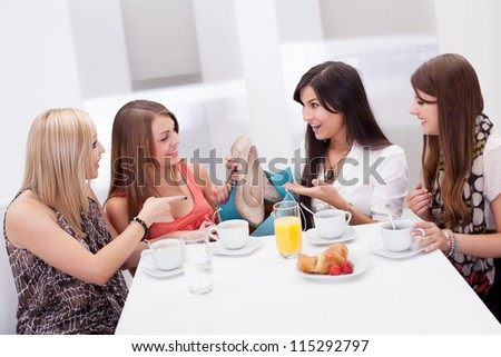 Women discussing footwear together seated at a morning coffee table as they compare their shopping purchases - stock photo
