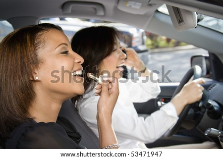Women distracted and laughing in car with cellphone and cosmetics. - stock photo