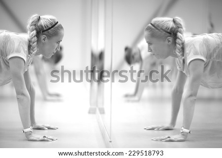 Women doing push-ups in front of the mirror, monochrome - stock photo