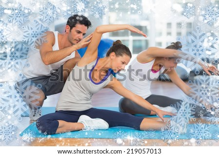 Women doing stretching exercises as trainer helps one against snow - stock photo