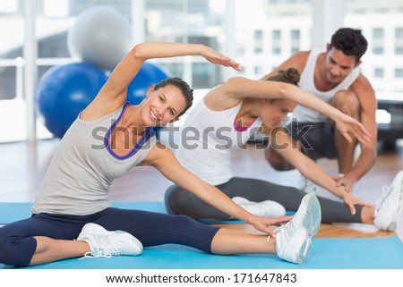 Women doing stretching exercises as trainer helps one at fitness studio - stock photo