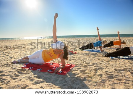 Women doing yoga exercise  Salamba Kapotasana or Supported Pigeon Pose on an empty beach - stock photo