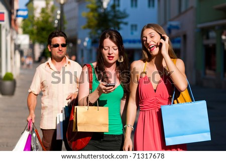 women downtown shopping with bags; a man is carrying the shopping bags - stock photo