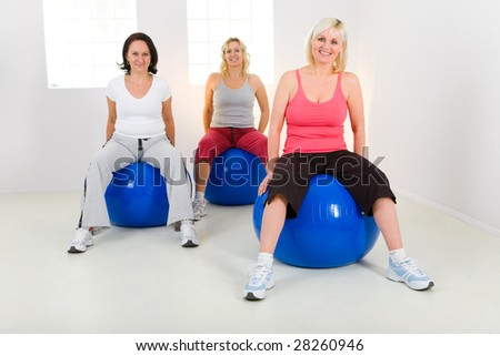 Women dresset sportswear working out on fitness ball. They're smiling and looking at camera. Front view. - stock photo