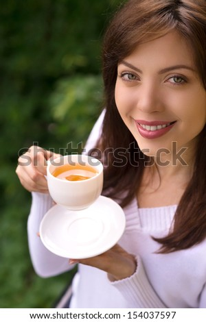 Women drinking coffee. Top view of beautiful young women holding a cup of coffee and looking away - stock photo