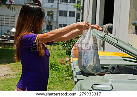 Women dumping garbage into the trash cans. - stock photo