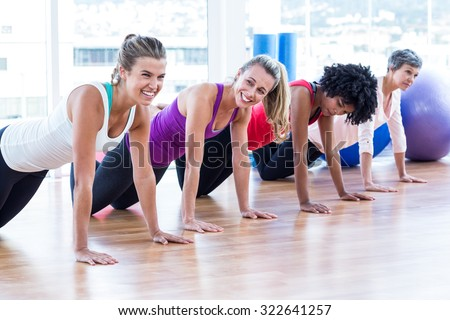 Women exercising on floor in fitness studio - stock photo