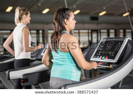 Women exercising on treadmill in the gym - stock photo