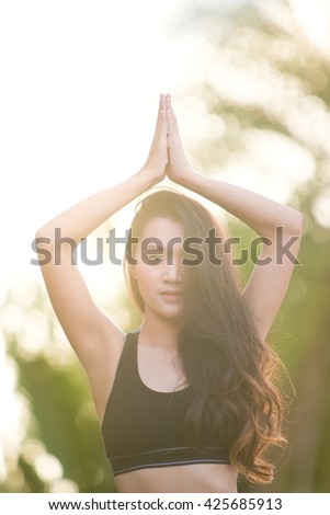 Women exercising practicing yoga in morning with sun light at garden - stock photo