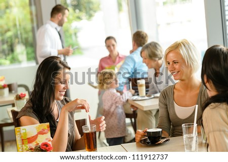 Women friends enjoying a drink at cafe talking happy relaxing - stock photo