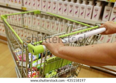 women hand push shopping cart ,supermarket , abstract blurred photo of store with trolley in department store blurred background, retail and shopping mall business. - stock photo