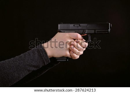 Women hand with a gun against a black background - stock photo