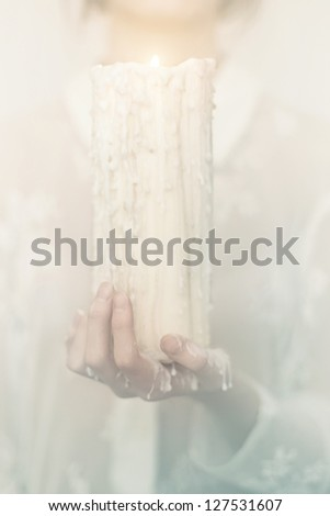 Women hands protect candlelight the mystical image of candles - stock photo