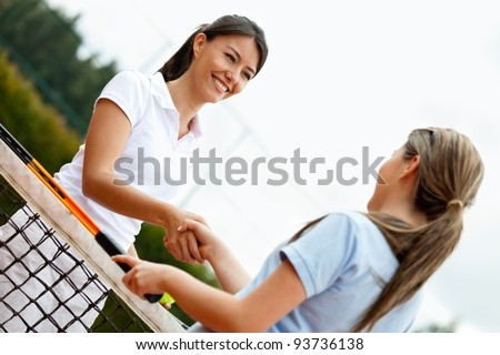 Women handshaking after playing a tennis match - stock photo