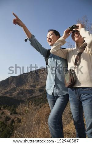 Women hiking, using binoculars, pointing at the mountain top - stock photo