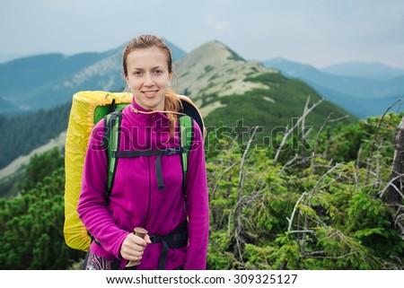 Women hiking with backpack holding trekking sticks high in the mountains - stock photo