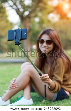 women hold monopod use smart phone take photograph selfie stick in park - stock photo