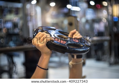 Women hold Weightlifting Plates or steel plates on hand in fitness gym background - stock photo