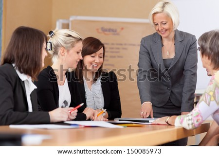Women in a business meeting seated around a table listening to their leader or manager giving a report - stock photo
