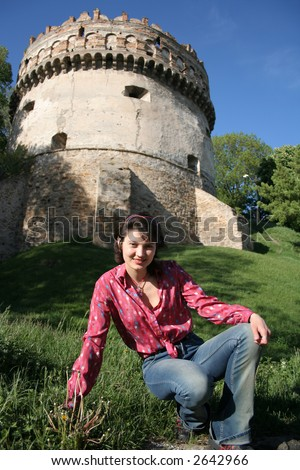 Women in a medieval place with castle ruin. - stock photo