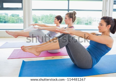 Women in boat pose in yoga class in fitness studio - stock photo