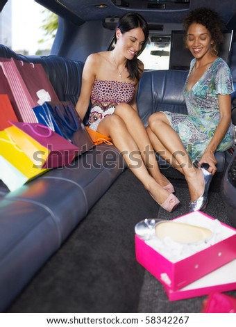 women in limousine trying on new shoes. Vertical shape, full length, copy space - stock photo