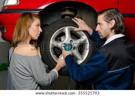 Women in male-dominated professions: Auto mechanic is guiding a female trainee in changing the tyre of a car in a garage. Concept for the fact that more and more women participate in jobs previously - stock photo