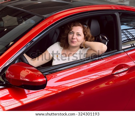 Women in the red car - stock photo