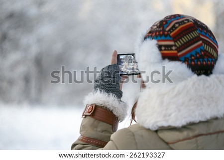 Women in winter clothing, fingerless mittens and ornamented hat photographing snowy forest by a mobile phone. Shallow dof. Focus on hand. - stock photo