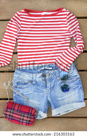 women jeans shorts on wooden background. focus on shirts - stock photo