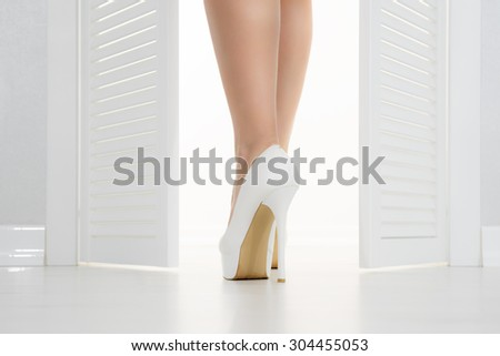 Women leg in white shoe looks out of the open door - stock photo
