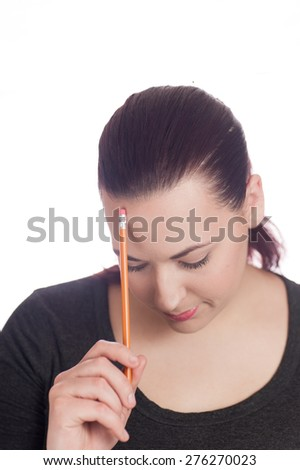 Women looking down resting pencil on forehead - stock photo