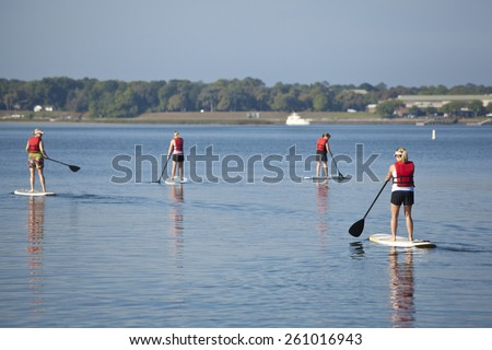 women paddleboarding on open water, focus on closest woman - stock photo