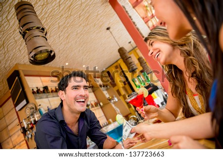 Women paying barman for drinks at the bar with cash and - stock photo