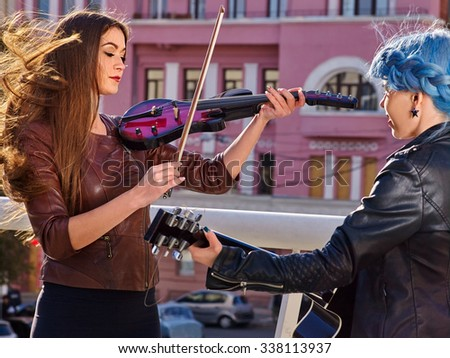 Women performer playing violin and guitar. Music street. - stock photo