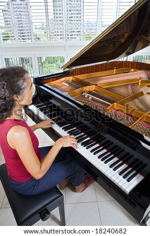 women pianist playing on a grand piano - stock photo