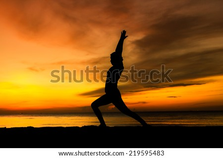 women playing yoga at beach side on sunset - stock photo