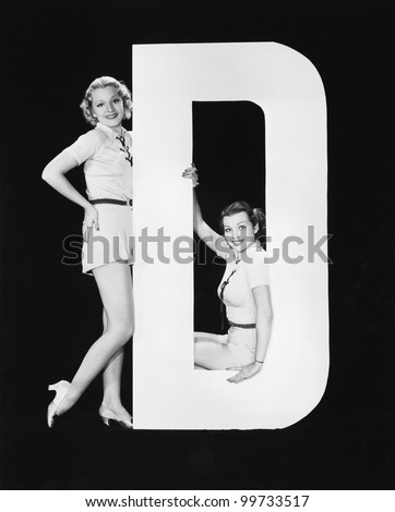 Women posing with huge letter D - stock photo