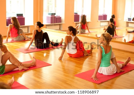 Women practicing yoga at health club - stock photo