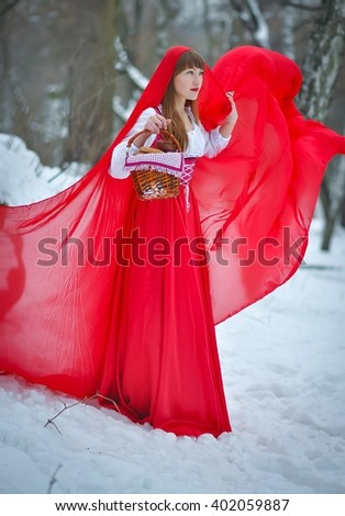 Women  red ridding hood with blond hair wearing a long red cloak and old red dress walks in winter forrest, A lovely young girl, among trees and snow, holding a pies with basket, fairy tales - stock photo